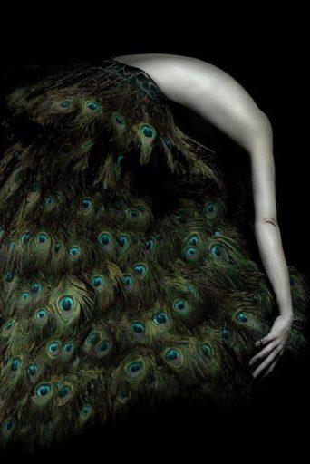 vrouw buigt in rok van pauwenveren